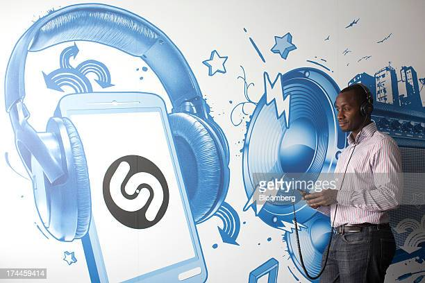 The Shazam Entertainment Ltd logo sits on a wall as an employee uses a smartphone in this arranged photo at the company's headquarters in London UK...