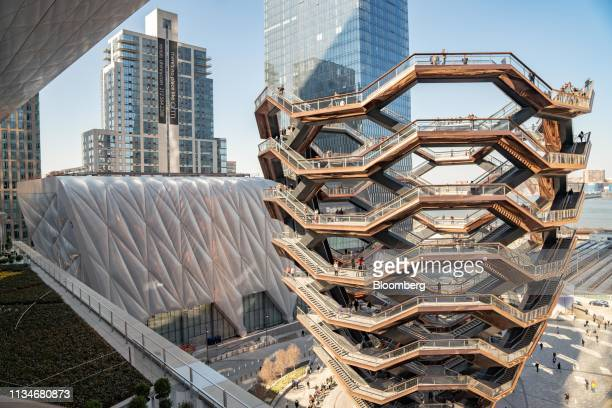 """The Shed cultural center stands behind the """"Vessel"""" sculpture, by Thomas Heatherwick, at Hudson Yards in New York, U.S., on Wednesday, April 3, 2019...."""