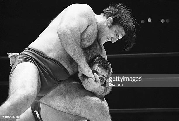 The Sheik had it easy. Caught here in a tight hold, the Syrian wrestler appears to be anything but comfortable. But The Shiek rallied and foiled...