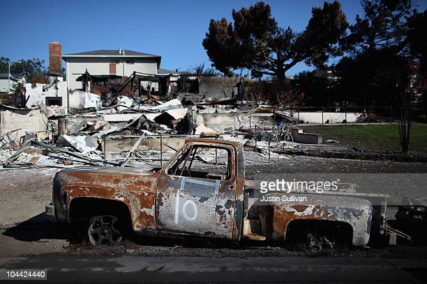 The shell of a truck sits in front of a burned home near the epicenter of the gas line explosion that devastated a neighborhood near San Francisco...