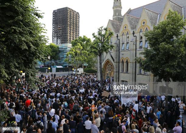 The shell of Grenfell Tower looms over protesters gathering at Notting Hill Methodist Church after marching back from Kensington Town Hall in west...