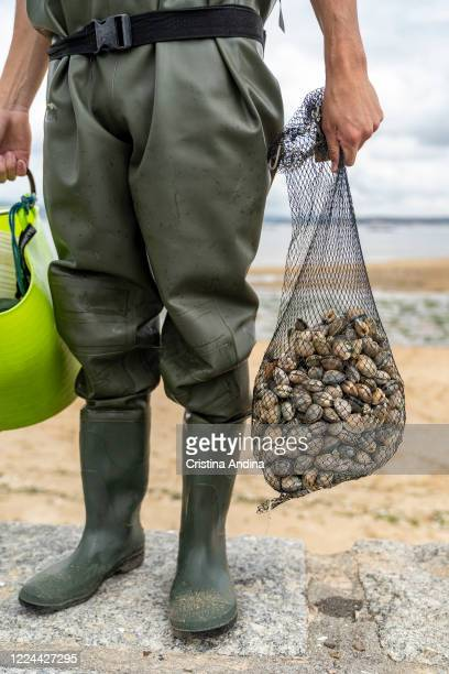 The shellfisherman Adrián González poses with a net bag with the clams he has collected on May 12 2020 in A Pobra do Caramiñal Spain The...