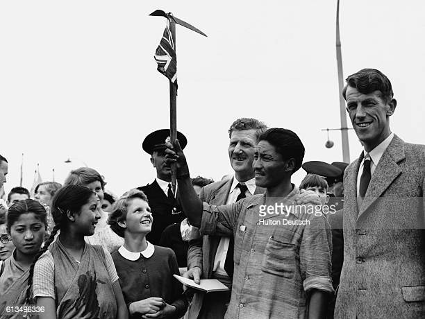 The Sherpa Tenzing Norgay holds aloft the ice axe which he and Sir Edmund Hillary used when they became the first people to successfully climb Mount...