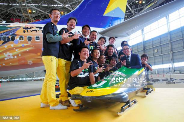The 'Shitamachi Bobsleigh' project members pose for photographs in front of their bobsled prior to its shipping to Jamaica at a hangar of Haneda...