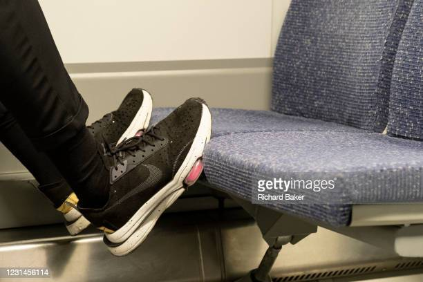 The shoes of a rail passenger rest on the fabric seats of train travelling through south London, on 26th February 2021, in London, England. Rail and...