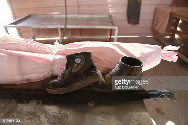 TOPSHOT The shoes of a Syrian boy are placed next to his shroudwrapped body at a morgue after he was killed in a reported government airstrike on the...