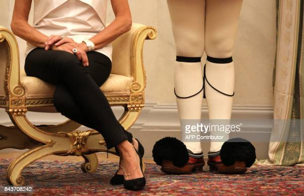 The shoes of French president's wife Brigitte Macron are pictured next to the Greek guard's shoes during a welcoming ceremony at the presidential...
