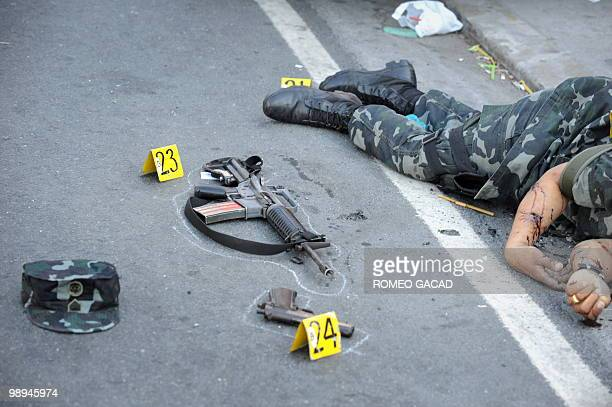 The shootout scene showing two firearms including the dead military security escort of congressional candidate Del Abaya are marked by police...