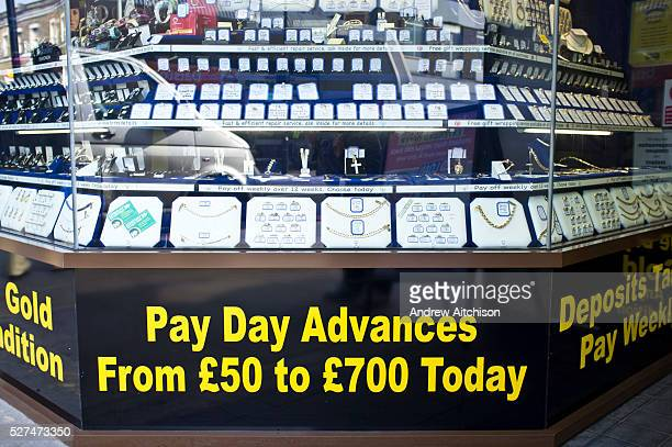 The shop front to a pawnbrokers in Dalston London UK The window display is full of gold and silver jewelry and below it is an advertisement for 'Pay...