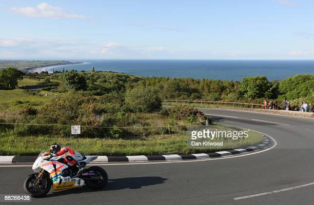 The shore off Ramsey catches the evening light in the distance as a competitor rides during a practice session on June 5 2009 on the Isle Of Man...
