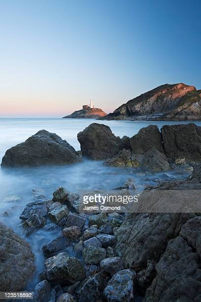 the shoreline at mumbles head with sunlight shining over the rocky coastline of the gower peninsula, swansea. - mumbles stock photos and pictures