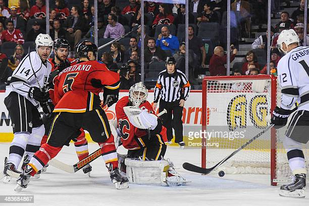 The shot of Anze Kopitar of the Los Angeles Kings flies past Karri Ramo of the Calgary Flames during an NHL game at Scotiabank Saddledome on April 9...