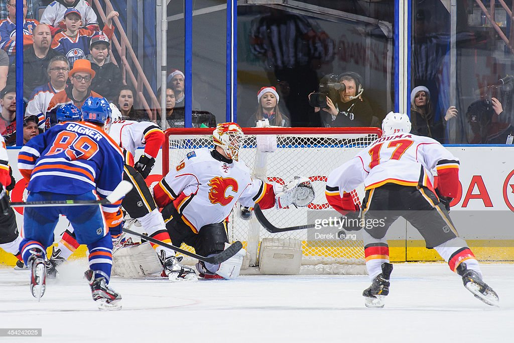 The shot of Taylor Hall #4 of the Edmonton Oilers flies past the defense of Reto Berra #29 of the Calgary Flames to tie the game and force overtime during an NHL game at Rexall Place on December 7, 2013 in Edmonton, Alberta, Canada. The Flames defeated the Oilers 2-1 in overtime.