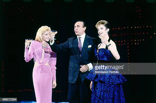 The showgirl Lorella Cuccarini the TV presenter Pippo Baudo Giuseppe Raimondo Vittorio Baudo and the actress dancer Alessandra Martines raising their...