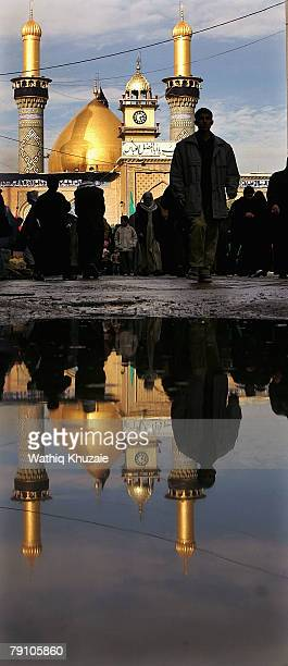 The Shrine of Imam Abbas brother of Imam Hussein reflects in a pool of water on January 18 2008 in the holy Shiite city of Karbala about 70 miles...