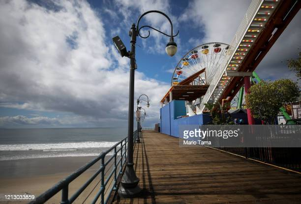 The shuttered Santa Monica Pier, a popular tourist destination, stands next to the Pacific Ocean on March 17, 2020 in Santa Monica, California....