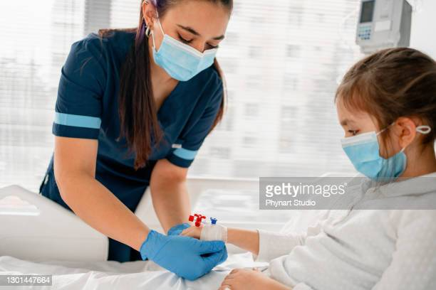 the sick child in the hospital bed , wearing a protective face mask - intensive care unit stock pictures, royalty-free photos & images