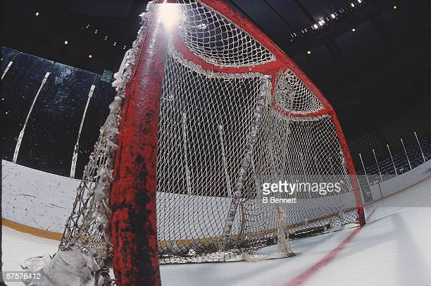 The side support and net of an ice hockey goal seen from below left February 1978