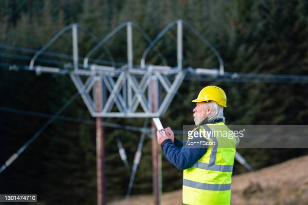 the side view of one man using a digital tablet while out working in the field - johnfscott stock pictures, royalty-free photos & images