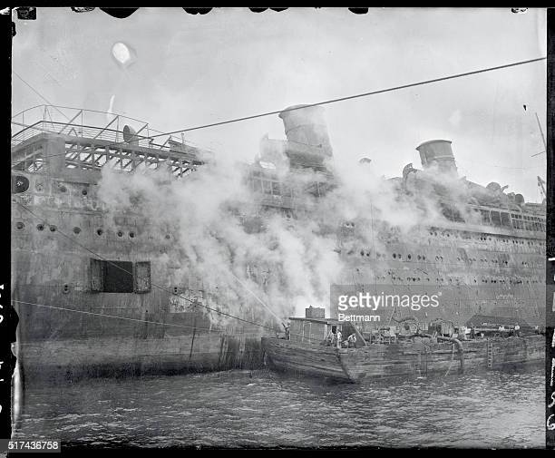 The sides of the fire scarred liner Morro Castle still are sizzling hot as is attested by this photography that shows the ship with hoses turned on...