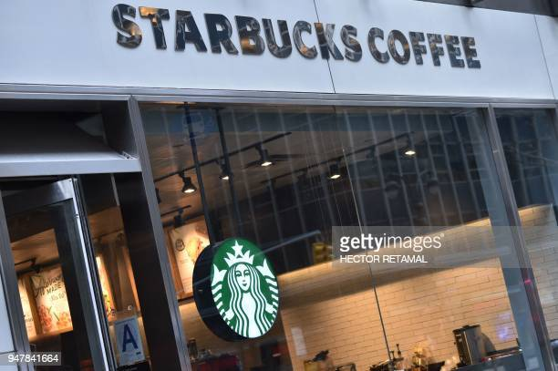 The sign for a Starbucks Coffee shop is seen in New York on April 17 following the company's announcement that they will close more than 8000 US...