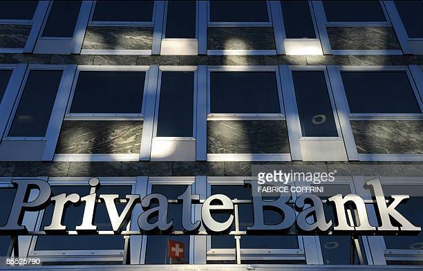The sign of a private bank with a Swiss flag reflected on the window's building is pictured on March 20 2009 in Geneva Switzerland will not appear on...