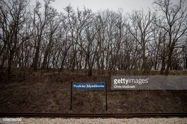 The sign of the Puskas Akademia train stop is seen on January 18, 2019 in Felcsut, Hungary. The vintage three car train with a wood-burning stove...
