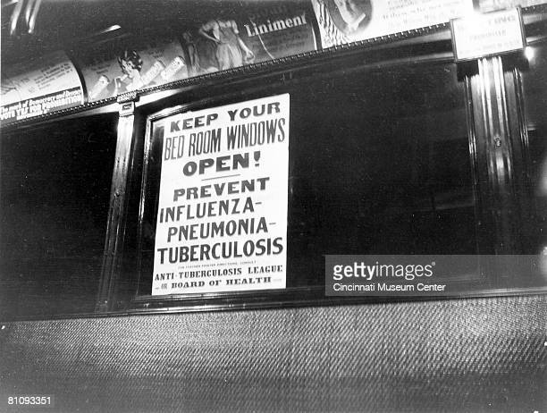 The sign reads 'Keep Your Bed Room Windows Open Prevent influenza pneumonia tuberculosis' and refers to the deadly 'Spanish Flu' pandemic that swept...