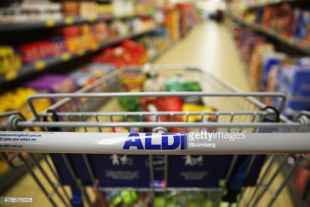 The signage for Aldi Stores Ltd is displayed on the handle bar of a shopping cart at one of the company's food store in Sydney Australia on Thursday...