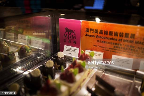 The signage for MGM Macau casino resort is displayed near cakes inside a display at the Pastry Bar at the MGM Macau casino resort operated by MGM...