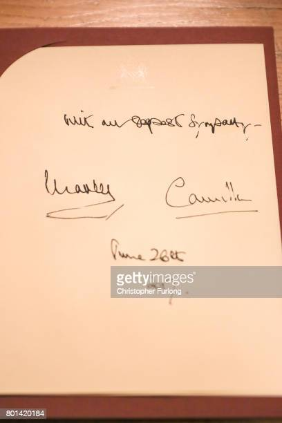 The signatures of Prince Charles Prince of Wales and Camilla Duchess of Cornwall wave goodbye to crowds after they signed a book of condolence during...