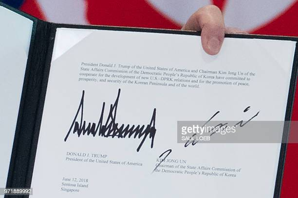 TOPSHOT The signatures of US President Donald Trump and North Korea's leader Kim Jong Un are seen on a document held up by Trump following a signing...