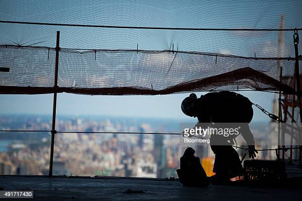 The silhouette of a construction worker is seen before the start of a topping out ceremony at 10 Hudson Yards in New York US on Wednesday Oct 7 2015...