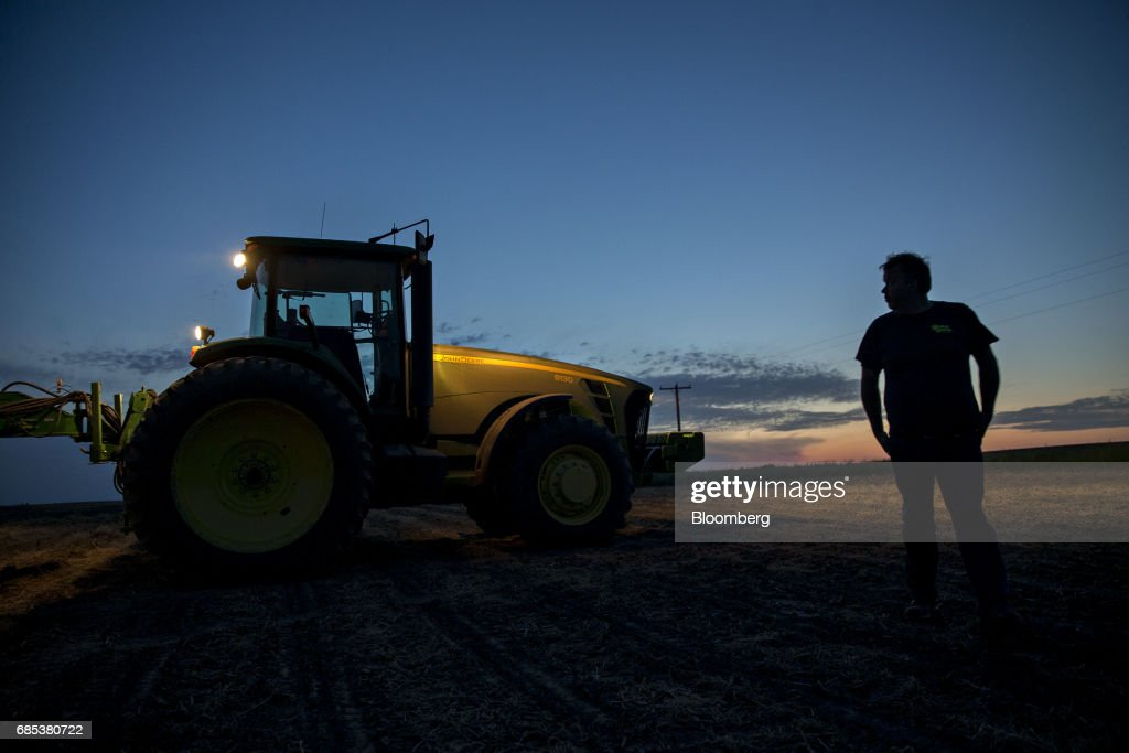 The silhouette of a farmer is seen standing in front of a John Deere & Co. tractor at night on a field in Malden, Illinois, U.S., on Tuesday, May 16, 2017. Rain in the Midwest and Great Plains will slow corn, soybean and wheat planting progress as well as curb seed germination and early growth, according to a senior meteorologist at the MDA Weather Services. Photographer: Daniel Acker/Bloomberg via Getty Images