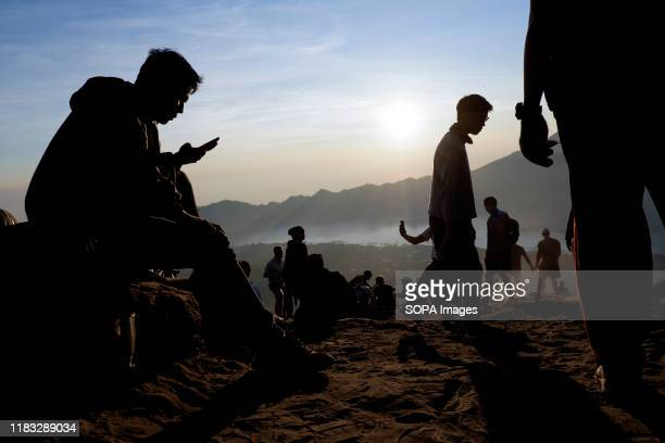 The silhouette of a group of hikers at the summit of Mount Batur in Bali during the sunrise A popular tourist destination Mount Batur is a 1717 meter...