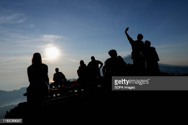 The silhouette of a group of hikers relaxing at the summit of Mount Batur in Bali during the sunrise A popular tourist destination Mount Batur is a...