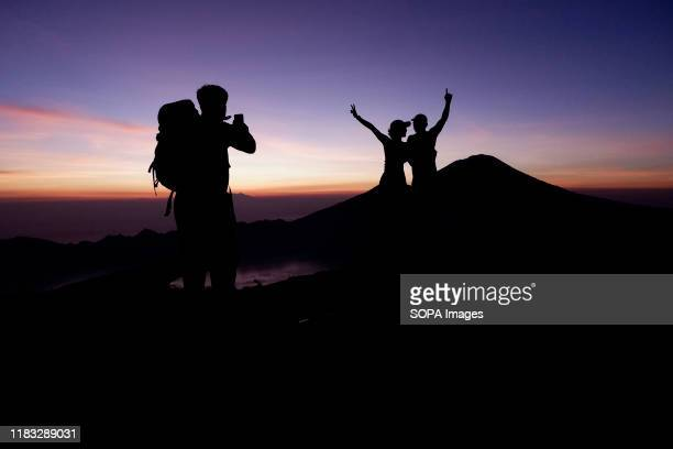 The silhouette of a group of hikers taking photos at the summit of Mount Batur in Bali during the sunrise A popular tourist destination Mount Batur...