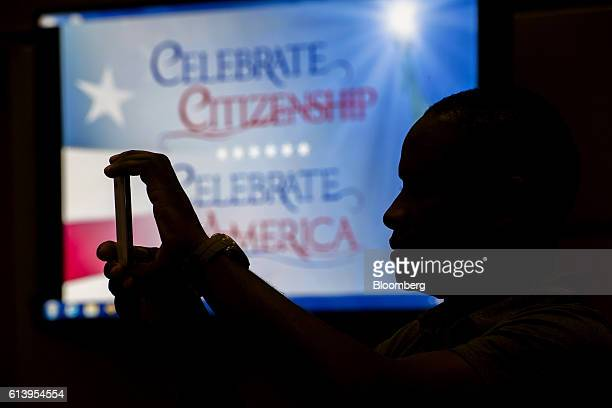 The silhouette of a man is seen using a smartphone to take a photograph during a naturalization ceremony at the Evo A DeConcini US Courthouse in...
