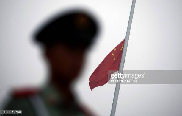 The silhouette of a paramilitary guard is seen as he stands at attention as the Chinese flag is raised during a ceremony at Tiananmen Square in...