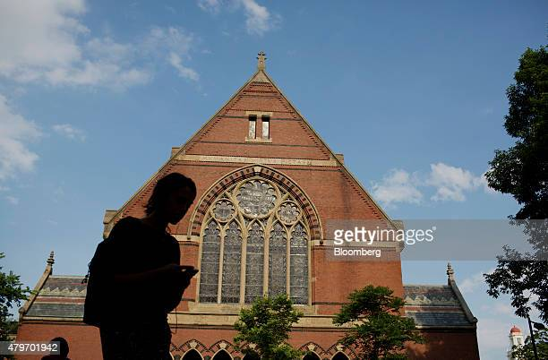 The silhouette of a pedestrian is seen passing Memorial Hall at the Harvard University campus in Cambridge Massachusetts US on Tuesday June 30 2015...