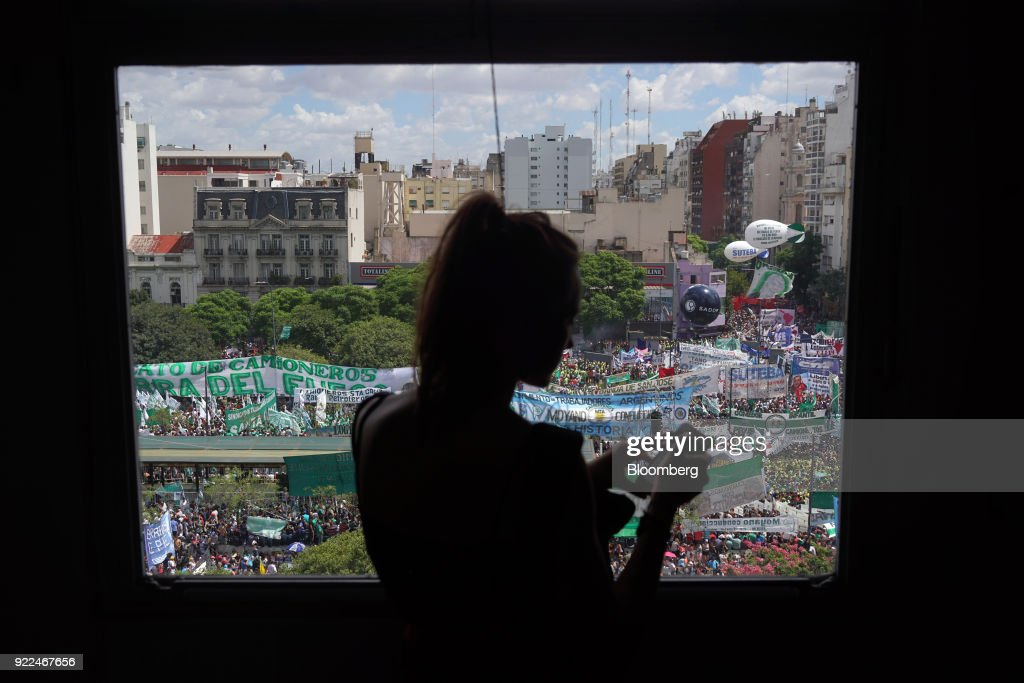 The silhouette of a person is seen in front of a window as demonstrators protest against President Mauricio Marci's economic policies in Buenos Aires, Argentina, on Wednesday, Feb. 21, 2018. Hugo Moyano, perhaps the most powerful union leader in the country, called the protest in a dispute over cuts to pension payments and dismissals as he heads for a showdown with Macri. The government claims it's a response to several allegations of corruption against Moyano. Photographer: Pablo E. Piovano/Bloomberg via Getty Images