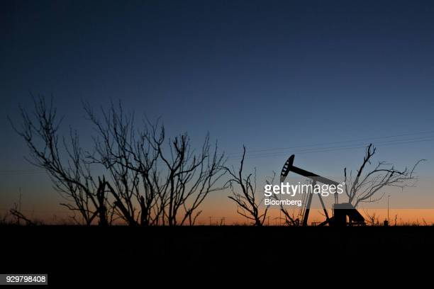 The silhouette of a pumpjack is seen at dusk in the Permian Basin near Midland Texas US on Friday March 2 2018 Chevron the world's thirdlargest...