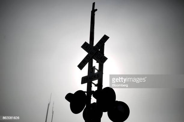 The silhouette of a railroad crossing gate is seen along tracks owned by CSX Corp in Worthville Kentucky US on Friday Oct 13 2017 CSX is scheduled to...