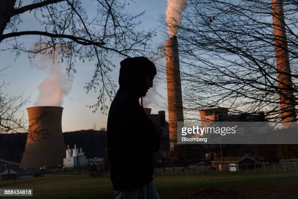 The silhouette of a resident is seen walking as the FirstEnergy Corp Bruce Mansfield coalfired power plant stands in Shippingport Pennsylvania US on...