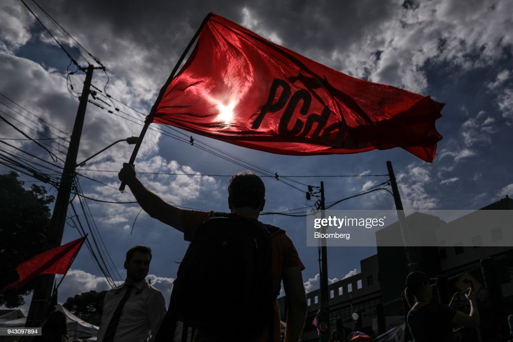 The silhouette of a supporter of former President Luiz Incio Lula da Silva is seen waving a flag while waiting at the Federal Police headquarters in Curitiba, Brazil, on Saturday, April 7, 2018. Lula said he will turn himself in to police, finally ending a tense stand-off with the authorities after he ignored a court-ordered deadline to begin a prison sentence. Photographer: Andre Coelho/Bloomberg via Getty Images