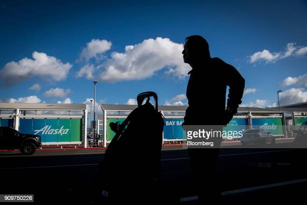 The silhouette of a traveler is seen in front of Alaska Air Group Inc signage at the Oakland International Airport in Oakland California US on Friday...