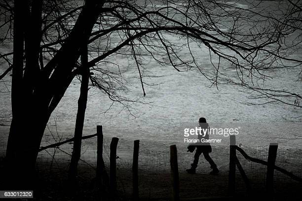 The silhouette of a walking woman is pictured in front of the frozen lake 'Grunewaldsee' on January 29 2017 in Berlin Germany