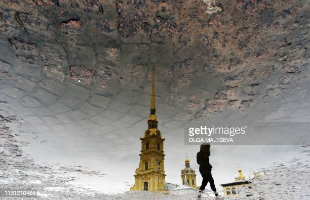 TOPSHOT The silhouette of a woman is reflected in a puddle as she crosses a square in front of the Peter and Paul Cathedral in Saint Petersburg on...