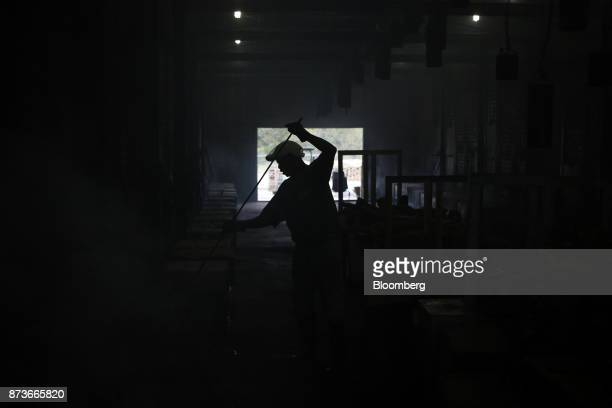 The silhouette of a worker is seen stoking fires in the smokehouse at the Greenberg Smoked Turkeys Inc facility in Tyler Texas US on Tuesday Nov 7...