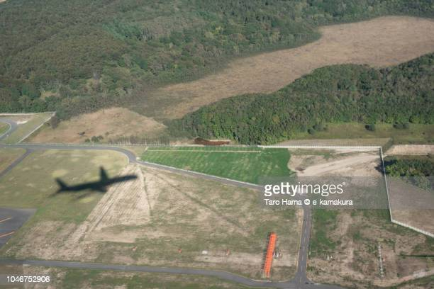 The silhouette of airplane taking off Hokkaido New Chitose Airport (CTS) in Japan daytime aerial view from airplane